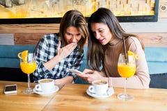 Deux jeunes amis féminins s'asseyant en café Photo stock