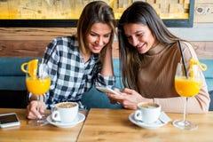 Deux jeunes amis féminins s'asseyant en café Photos stock