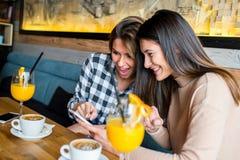 Deux jeunes amis féminins s'asseyant en café Images libres de droits