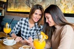 Deux jeunes amis féminins s'asseyant en café Photographie stock