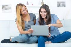 Deux jeunes amis féminins s'asseyant sur le sofa Images libres de droits