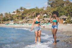 Deux jeunes amis féminins se tenant dans parler de l'eau Photo stock