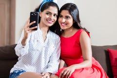 Deux jeunes amis faisant des photos de selfie à l'intérieur Images stock