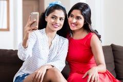 Deux jeunes amis faisant des photos de selfie à l'intérieur Photo libre de droits