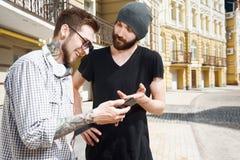 Deux jeunes amis gais parlent dans la ville Image stock