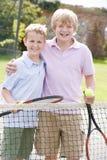 Deux jeunes amis mâles sur le sourire de court de tennis Image stock