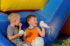 Deux jeunes amis mangeant la soie de sucrerie Photo stock
