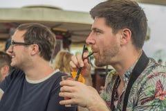Deux jeunes amis masculins ayant l'amusement, les cocktails potables et causant avec des amis sur le café de terrasse en ville Photographie stock libre de droits