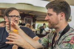 Deux jeunes amis masculins ayant l'amusement, les cocktails potables et causant avec des amis sur le café de terrasse en ville Photos stock