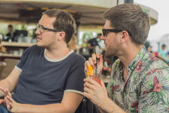 Deux jeunes amis masculins ayant l'amusement, les cocktails potables et causant avec des amis sur le café de terrasse en ville Image libre de droits