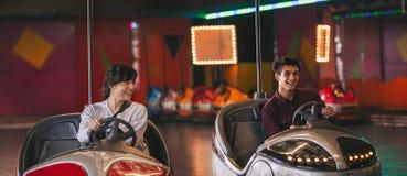 Deux jeunes amis montant les voitures de butoir au parc d'attractions Image libre de droits