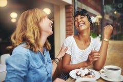 Deux jeunes amis multi-ethniques appréciant le café Images stock