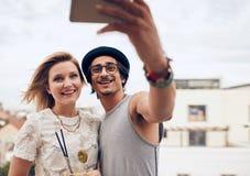 Deux jeunes amis prenant l'autoportrait à la partie Photos stock