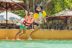Deux jeunes amis sautant dans la piscine Image libre de droits