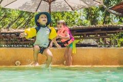 Deux jeunes amis sautant dans la piscine Photos libres de droits