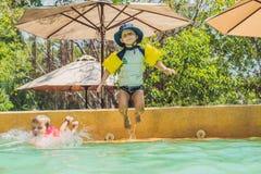 Deux jeunes amis sautant dans la piscine Images libres de droits