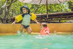 Deux jeunes amis sautant dans la piscine Photographie stock libre de droits