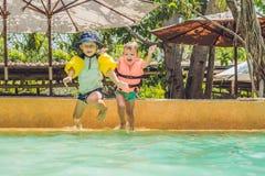Deux jeunes amis sautant dans la piscine Images stock
