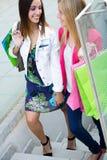 Deux jeunes amis sur les étapes du stationnement dans un afternoo d'achats Photos stock