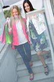 Deux jeunes amis sur les étapes du stationnement dans un afternoo d'achats Photos libres de droits