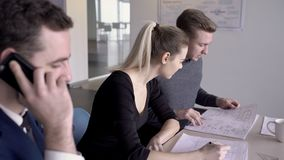 Deux jeunes architectes discutent le modèle de bâtiment et l'homme d'affaires parle à l'associé au téléphone dans banque de vidéos