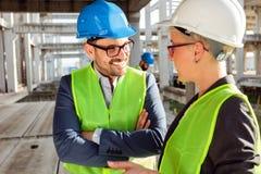 Deux jeunes architectes modernes ou ingénieurs civils parlant du futur développement de projet sur un chantier de construction photos stock
