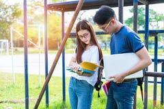Deux jeunes asiatiques d'université discutant au sujet du livre de lecture et Image stock