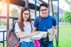 Deux jeunes asiatiques d'université discutant au sujet du livre de lecture et Photographie stock libre de droits