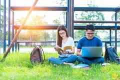 Deux jeunes asiatiques d'université discutant au sujet du livre de lecture et Images stock