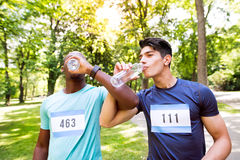 Deux jeunes athlètes se sont préparés à la course, eau potable  Photo libre de droits