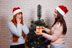 Deux jeunes beaux amis dans des chapeaux de Santa avec un boîte-cadeau sur le chr Photos stock