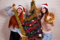 Deux jeunes beaux amis dans Santa couvre décorer Noël t Photos stock