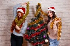 Deux jeunes beaux amis dans Santa couvre décorer Noël t Image libre de droits