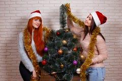Deux jeunes beaux amis dans Santa couvre décorer Noël t Images libres de droits