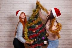 Deux jeunes beaux amis dans Santa couvre décorer Noël t Photo stock
