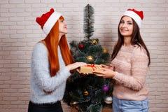 Deux jeunes beaux amis dans Santa couvre partager des cadeaux sur Chris Image libre de droits
