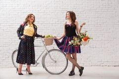Deux jeunes belles amies intelligentes avec une bicyclette et un panier des fleurs rencontrées et du bavardage Photo stock