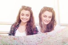 Deux jeunes belles brunes regardant sur la carte et recherchant quelque chose Photos stock