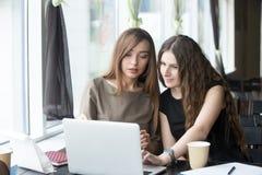 Deux jeunes belles femmes causant en café Image libre de droits
