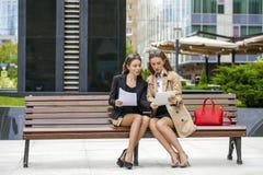 Deux jeunes belles femmes d'affaires s'asseyant sur un banc Photographie stock libre de droits