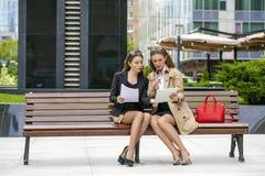 Deux jeunes belles femmes d'affaires s'asseyant sur un banc Photos libres de droits