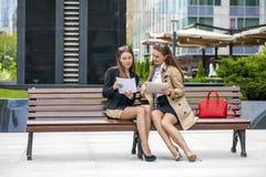 Deux jeunes belles femmes d'affaires s'asseyant sur un banc Image libre de droits