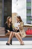 Deux jeunes belles femmes d'affaires s'asseyant sur un banc Images stock