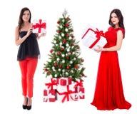 Deux jeunes belles femmes en rouge avec de grands boîte-cadeau et decorat Image libre de droits