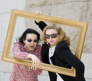 Deux jeunes belles femmes européennes d'affaires en verres foncés dans un cadre de tableau. Photo libre de droits