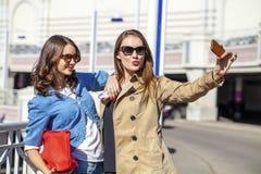 Deux jeunes belles femmes heureuses dans des lunettes de soleil Image libre de droits