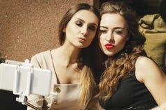 Deux jeunes belles femmes heureuses faisant le selfie dehors Photographie stock