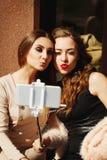Deux jeunes belles femmes heureuses faisant le selfie dehors Photo stock