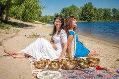 Deux jeunes belles femmes jouant des cuvettes de chant de Tibétain en nature sur la berge Photographie stock libre de droits