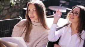 Deux jeunes belles femmes regardant le menu en restaurant, pages de rotation et choisissant des plats pour le petit d?jeuner banque de vidéos